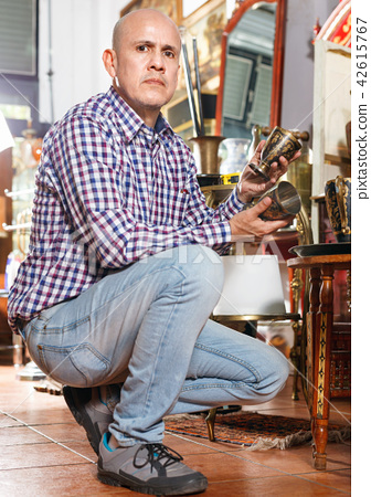 Portrait of successful owner of antiques shop among vintage things 42615767