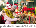 Woman with daughter looking at floral decoration at Cristmas fair 42615816