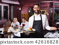 Smiling young cheerful waiter taking care of adults 42616828