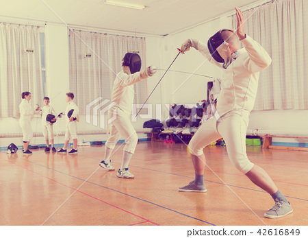 Adults and teens wearing fencing uniform practicing with foil 42616849