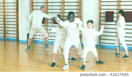 Focused boys fencers attentively listening to professional fencing coach in gym 42617000