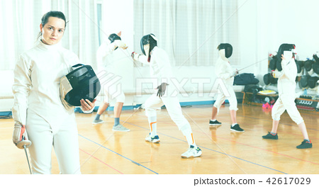 Portrait of smiling sporty young woman with foil at fencing workout 42617029