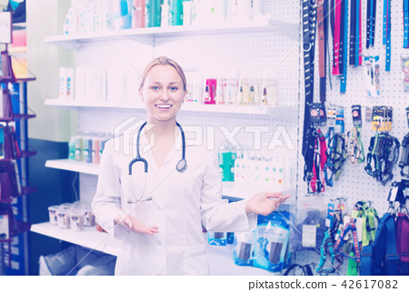 Female vet advising on pet cosmetics in pet store 42617082