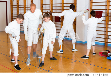 Focused boys fencers attentively listening to professional fencing coach in gym 42617166