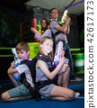 Boy and girl sitting back to back with laser pistols 42617173