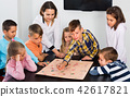 Boys and little girls playing at board game 42617821