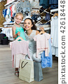portrait of woman and girl shopping kids apparel in clothes store 42618448