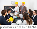 Positive professionals with laptops and helmets 42618766