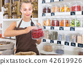 Young woman is offering dried flowers of Hibiscus in container 42619926