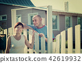 woman and man near fence wicket 42619932
