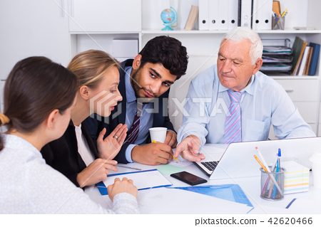 Managers are writing financial reports and discussing with mature boss 42620466