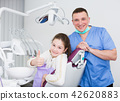 Male dentist with satisfied girl 42620883