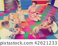 Kids sitting around teacher with small guitar 42621233