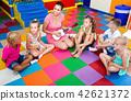 Children listening teacher playing small guitar at classroom 42621372