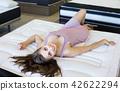 Young woman customer enjoying on soft mattress 42622294