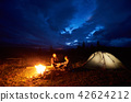 Couple man and woman tourists having a rest at night camping in the mountains under cloudy sky 42624212