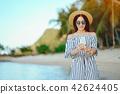 girl waking along the beach using her phone 42624405
