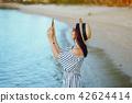 girl waking along the beach using her phone 42624414