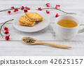 Tea, tea leaves on wooden spoon and biscuit  42625157