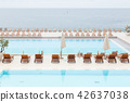 Luxury swimming pool with wooden deck chairs. 42637038