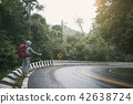 Travel man hitchhiker on road in mountain sunset 42638724