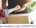 woman appending signature sign on smartphone after receive boxes from delivery man shopping 42640751