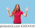 The young emotional angry and scared woman standing and looking at camera 42654439