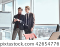 Businesspeople at office working together standing using smartph 42654776