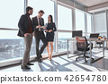 Businesspeople at office working together standing man browsing  42654780