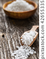 Sea salt on wooden plate and spoon on table  42655335