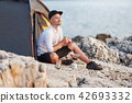 Man sitting with an iron cup on rocky coast of sea. 42693332
