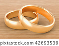 Golden wedding rings on the wooden table 42693539