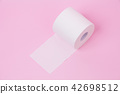 The roll of white toilet tissue paper on pink back 42698512