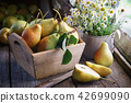 Fresh pears in wooden crate, bouquet of daisies. 42699090