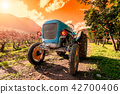 Sunset on an old light blue tractor 42700406