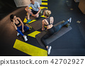 Positive couple is stretching with coach in gym 42702927