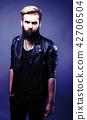 portrait of young bearded hipster guy on gray dark background cl 42706504