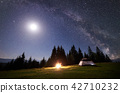 Night camping in mountains. Tourist tent by campfire near forest under blue starry sky, Milky way 42710232