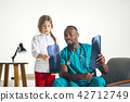 Young african male pediatrician explaining X-ray to child 42712749