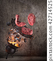 Kettle grill with hot briquettes, cast iron grate and tasty beef steaks flying in the air. 42714525