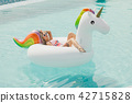 beautiful slim girl in a swimsuit. Floating on a big white beach inflatable unicorn pool 42715828