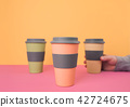Hand holding take away coffee cup. 42724675