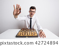 Portrait of a young man in a studio, playing chess and holding a king chessman. 42724894