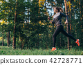 Portrait of young female athlete wearing tracksuit running in forest 42728771