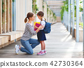 first day at school. mother leads  little child school girl in f 42730364