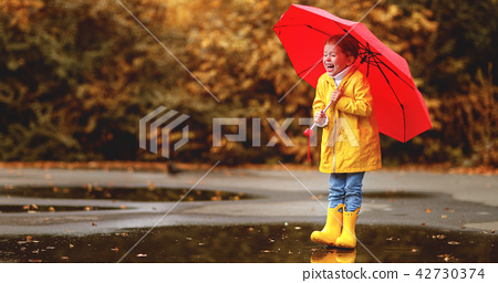happy child girl with an umbrella and rubber boots in puddle  o 42730374