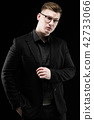 Portrait of confident handsome elegant responsible businessman with hand on his jacket on black 42733066
