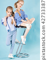 Girls twins in light blue clothes are posing near a bar stool on a blue background. 42733387