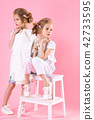 Twins girls in bright clothes posing near the stairs with two steps on a pink background. 42733595