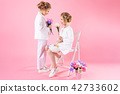 Twins girls in light clothes with bouquets of flowers posing near a chair on a pink background. 42733602